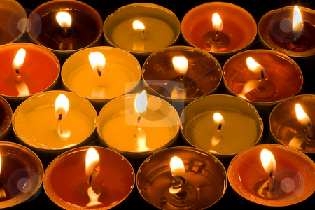 Burning Candles stock photo, A group of burning candles on the black background by Petr Koudelka