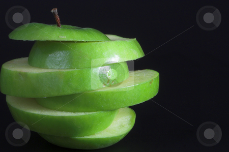 Sliced Apple stock photo, A sliced green apple in a stack. by Robert Byron