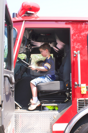 Boy Sitting In Fire Truck stock photo, A young boy sitting in a fire truck. by Robert Byron