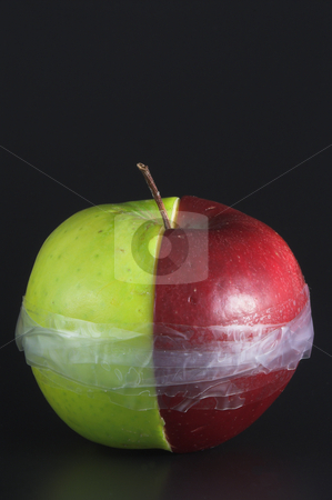 Taped Apple stock photo, Red and green apple halves taped together. by Robert Byron