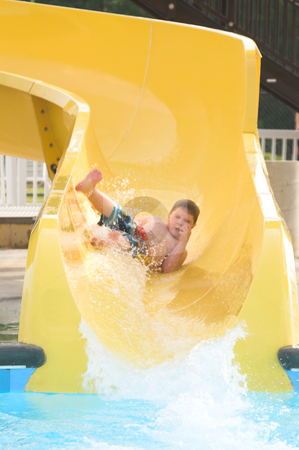 Boy at a Water Park stock photo, A young boy sliding down a water slide. by Robert Byron