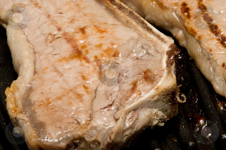 Steak stock photo, Delicious steaks cooking on an inside grill. by Robert Byron