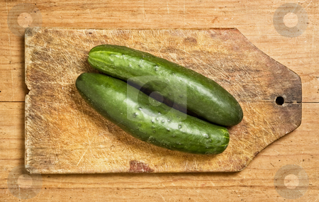Two cucumbers stock photo, Two cucumbers on a wooden kitchen table. by Pablo Caridad