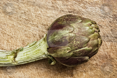 Fresh artichoke stock photo, Artichoke on a wooden cutting table, studio shot. by Pablo Caridad