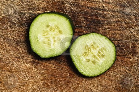Slices of cucumber  stock photo, Slices of cucumber on a wooden background. by Pablo Caridad
