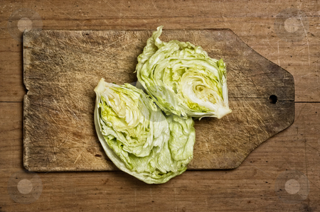 Fresh lettuce stock photo, Cut fresh lettuce on old wooden table. by Pablo Caridad