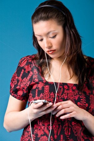 Girl with a mp3 player stock photo, Young girl is busy with her mp3 player by Frenk and Danielle Kaufmann