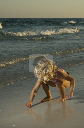 Beach Discovery stock photo, A 4 year old girl in a swimsuit discovering wonders in the beach sand at sunset. by A Cotton Photo