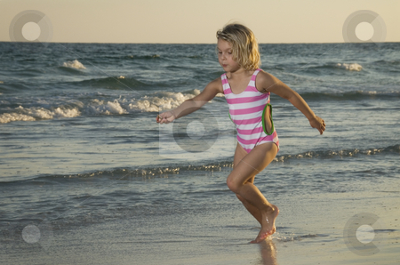 Little girl running on beach stock photo, Little girl running on beach by A Cotton Photo