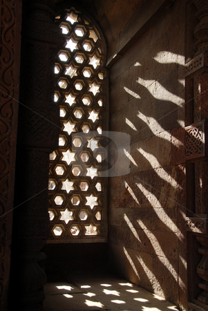 Star Window of India stock photo, The sun shining through the ornately carved stone window inside the Alai Darwaza. The Alai Darwaza was built in 1311 to serve as the southern entrance to the Qutab Minar, one of the largest standing stone minarets in the world. by A Cotton Photo