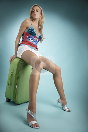 Female model resting on green suitcase stock photo, Blonde female model sitting on a green suitcase with a aqua blue background by Luca Mosconi
