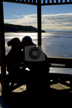 Silhouette of two people kissing stock photo, Happy couple kissing by the ocean view by Vlad Podkhlebnik
