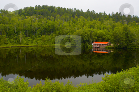 Red house stock photo, A small red house by a calm lake by Vlad Podkhlebnik