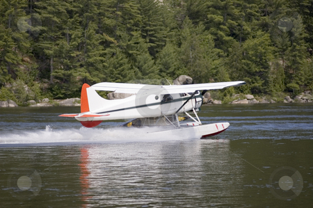 Water plane stock photo, White water plane landing on a river by Vlad Podkhlebnik