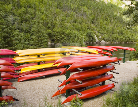 Kayaks stock photo, A bunch of yellow and red stacked kayaks by Vlad Podkhlebnik