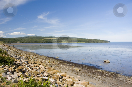 Rocky beach stock photo, View of a rocky beach with mountains in the background by Vlad Podkhlebnik
