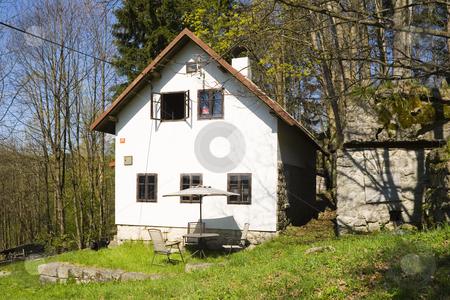 House on the mountain meadow stock photo, A little white house on a mountain meadow among woods by Petr Koudelka