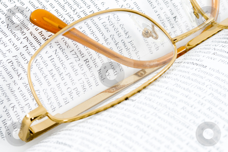 Glasses on Books stock photo, Glasses lying on an open book - close up by Petr Koudelka