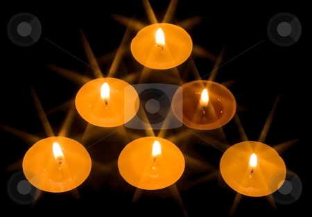 Triangle of Candles stock photo, A group of six burning candles on the black background by Petr Koudelka