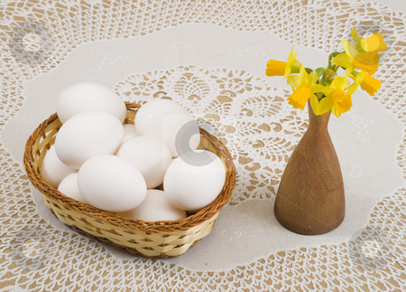 Easter stock photo, A basket of eggs and yellow daffodils in a vase by Petr Koudelka