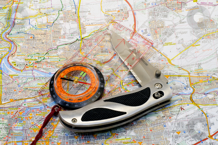 Compass and knife on a map stock photo, A compass and a knife lying on a map - close up by Petr Koudelka