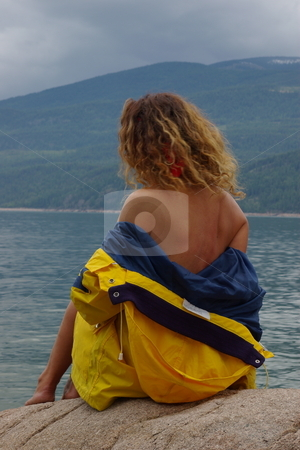 Rain coats stock photo, Semi nude female fashion model wearing a yellow rain coat by Rick Olson