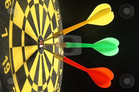 Three colourful darts in the bullseye. stock photo, Three colourful darts in the bullseye. by Stephen Rees