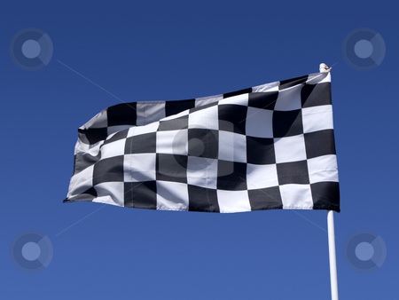 A checkered flag blowing in the wind at the end of a motor race. stock photo, A checkered flag blowing in the wind at the end of a motor race. by Stephen Rees