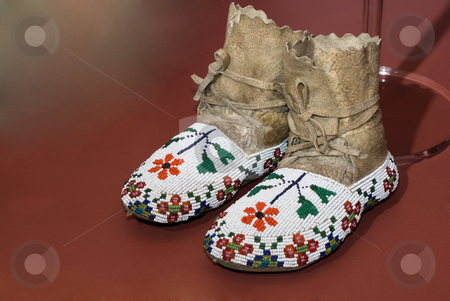 Native American Moccasins stock photo, A pair of Native American moccasins sitting on a red floor by Richard Nelson