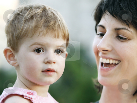 Brunette Mother and child stock photo, Baby girl in the arms of a happy smiling mother outdoors by Claudia Veja