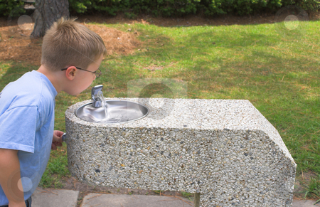 Boy at Water Fountain stock photo, A young boy drinking from a water fountain. by Robert Byron