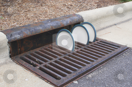 Drying Plates stock photo, Plates drying in a storm drain grate. by Robert Byron
