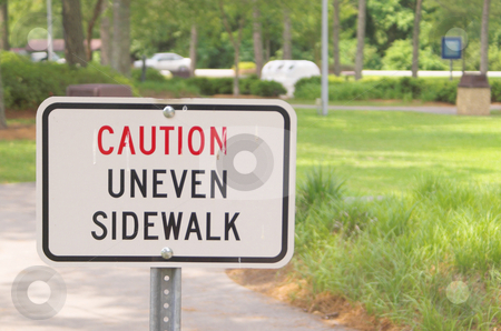 Caution Uneven Sidewalk stock photo, A sign in a park stating Caution Uneven Sidewalk by Robert Byron
