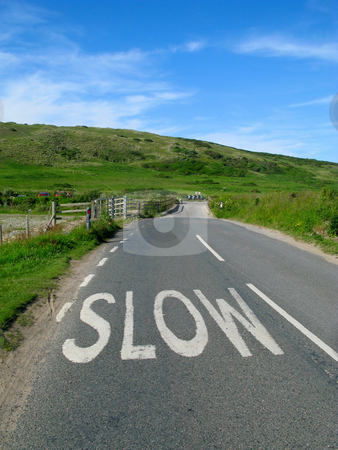 Slow sign on an English countryside road. stock photo, Slow sign on an English countryside road. by Stephen Rees