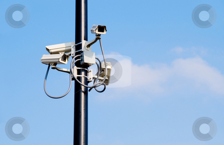 Security Cameras stock photo, A series of security cameras on a mounpole. by Robert Byron