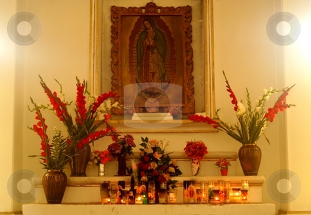 Religious altar with flowers and candles stock photo, Catholic altar with flowers and candles, showing religious artwork in the background by Wes Shepherd