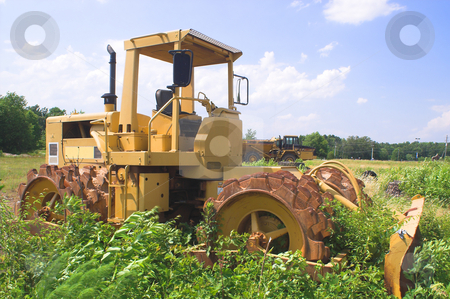 Abandoned Bulldozer stock photo, An abandoned bulldozer sitting in a field of weeds. by Robert Byron