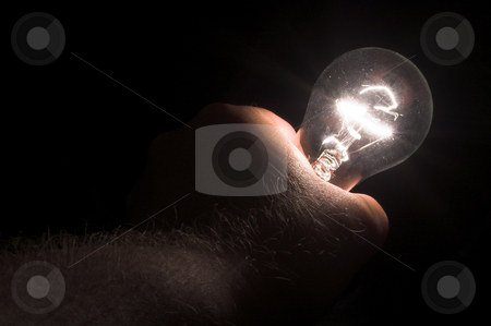 Holding a Light Bulb stock photo, A person powering a light bulb by holding it. by Robert Byron