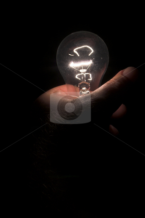 Hand gripping Light Bulb stock photo, A person powering a light bulb by holding it. by Robert Byron