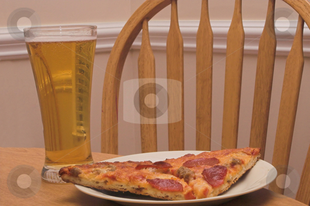 Pizza and Beer stock photo, A slice of pizza and a beer in a pilsner glass. by Robert Byron