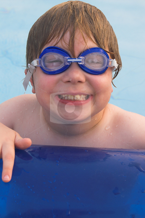 Boy Swimming stock photo, A little boy resting on the edge of a pool. by Robert Byron