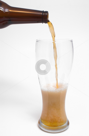 Pouring Beer stock photo, A golden colored beer being poured into a pilsner glass. by Robert Byron