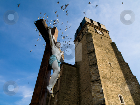 Jesus christ crucifix stock photo, Jesus christ crucifix in front of a Church in France with flying birds by Laurent Dambies