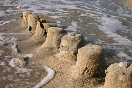 The ruins of a sand castle being swept away by the sea stock photo, The ruins of a sand castle being swept away by the sea by Stephen Rees