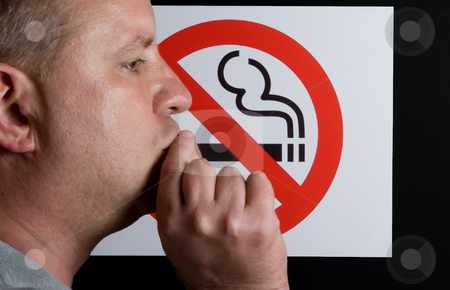 No Smoking Sign stock photo, A man smoking a no smoking sign. by Robert Byron