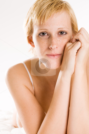 Beautiful blond in lingerie making eye contact stock photo, Studio portrait of a blond short haired girl in lingerie laying on her bed looking at you by Frenk and Danielle Kaufmann