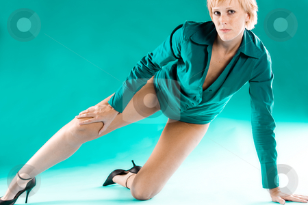 Blond girl in green blouse stretching her leg stock photo, Portrait of a blond girl in a green blouse posing by Frenk and Danielle Kaufmann