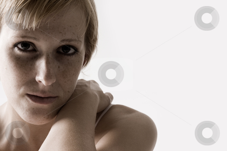 Close portrait of a sad looking blond stock photo, Studio portrait of a blond short haired girl looking sad by Frenk and Danielle Kaufmann