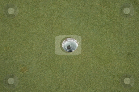 Golf hole stock photo, The round hole on a golf course green by Tim Markley