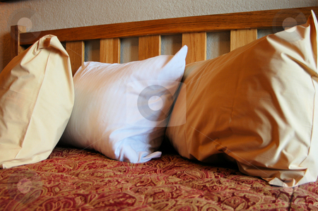 Hotel bed stock photo, Three pillows on a bed in a hotel room by Tim Markley